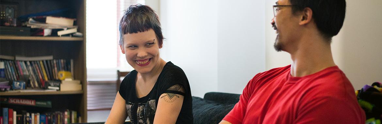 Nainen ja mies nauravat sohvalla