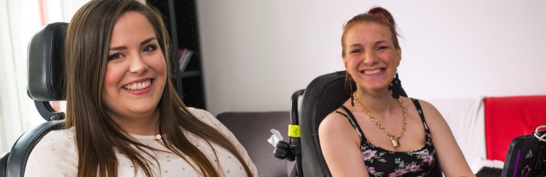Kaksi naista istuu toimistossa ja hymyilee