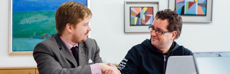 Kaksi kättelevää miestä toimistossa