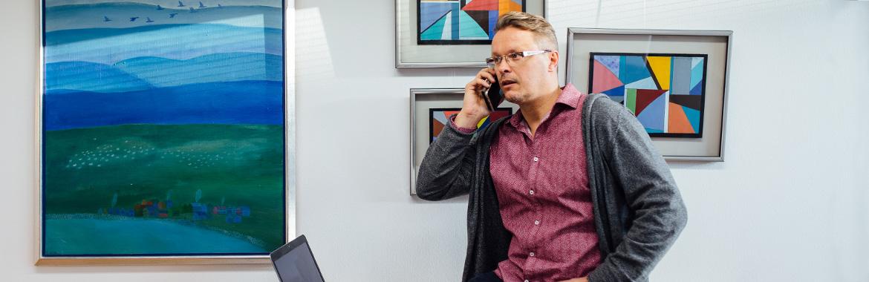 Mies seisoo ja puhuu puhelimessa